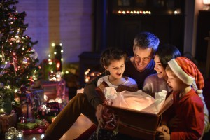 lovely family opening a gift on Christmas night near the wood stove and lit Christmas tree, enjoying the warm atmosphere of Christmas, one child wears a hat of Santa Claus